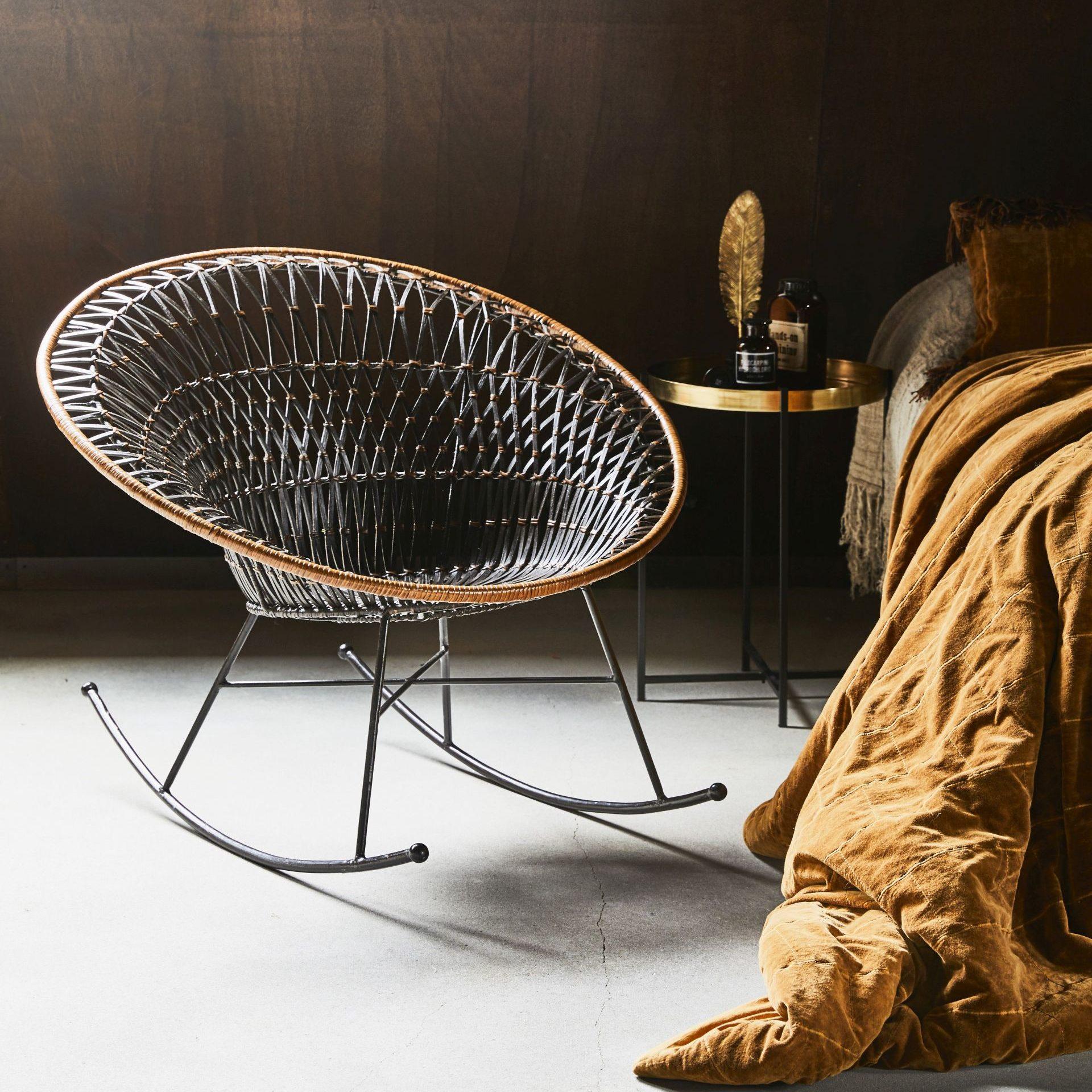 Fotel rattanowy bujany z oferty HK Living w cenie 1 899 zł, narzuta na łóżko w kolorze musztardowym (wymiary 230×250 cm) 1 699 zł, stolik z metalową tacą i mosiężną ramą (średnica 40, wysokość 63 cm) 599 zł. www.dutchhouse.pl